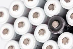 Des batteries d'aa sont situées près de l'un l'autre Plan rapproché de toutes les batteries blanches, excepté une noire, sur un f images stock