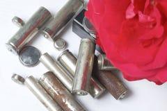 Des batteries de rebut de différents types sont dispersées Avec une fleur rouge de rose Images libres de droits