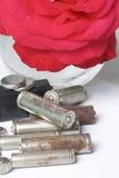 Des batteries de rebut de différents types sont dispersées Avec une fleur rouge de rose Photos libres de droits