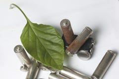 Des batteries de rebut de différents types sont dispersées Couvert de feuille juteuse verte Photos stock