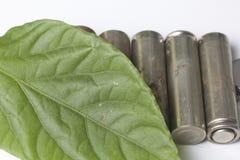 Des batteries de rebut de différents types sont dispersées Couvert de feuille juteuse verte Image libre de droits