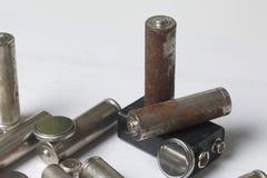 Des batteries de rebut de différents types sont dispersées Sur un fond blanc Photo stock