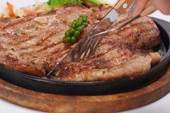 Des biftecks sont coupés avec un couteau Photo stock