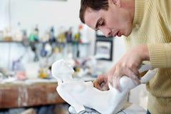 Des Bildhauers Befestigungsfahrwerkbeine sorgfältig zur Statuette Stockfotos