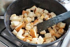 Des biscuits sont faits frire dans une casserole images libres de droits