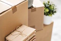 Des boîtes en carton avec des choses sont empilées sur le plancher dans la perspective d'une fin blanche de mur  Livres et table image libre de droits