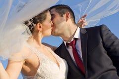 Des Bonbon-Küssen eben verheirateten Paars im Freien Stockfotografie