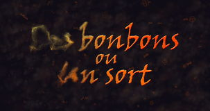 Des bonbons uo un sort (Trick or Treat) French text dissolving into dust from left Stock Photography