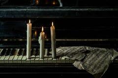 Des bougies sont allumées sur le piano avec la musique images stock