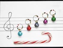 Des boules de décoration de Noël sont arrangées sur un morceau de papier comme des notes de musique Images libres de droits