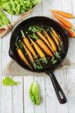 Des carottes fraîches sont faites frire dans une poêle Photos stock