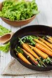 Des carottes fraîches sont faites frire dans une poêle Photos libres de droits