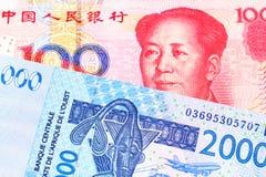 Des cent notes chinoise de yuans avec la facture d'Afrique occidentale de franc photographie stock