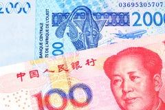 Des cent notes chinoise de yuans avec la facture d'Afrique occidentale de franc images libres de droits