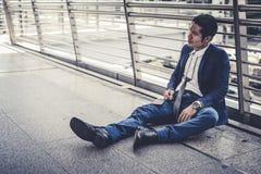 Des chômeurs d'homme d'affaires de la société s'asseyant sur la rue, il est se sentir de soumis à une contrainte et la tristesse, photographie stock libre de droits