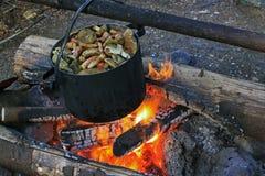 Des champignons sont faits cuire dans une vieille casserole en métal photographie stock