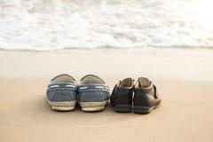 Des chaussures plus lointaines et des chaussures du fils sur le beac de thes Photographie stock
