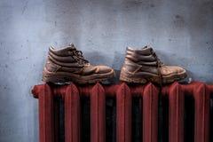 Des chaussures sont séchées sur la batterie de chauffage images libres de droits