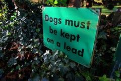 Des chiens doivent être gardés sur un signe d'avance Photographie stock libre de droits