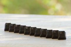 Des clés noires du clavier se compose la rédaction publicitaire de mot sur une table blanche en plein air Photo stock