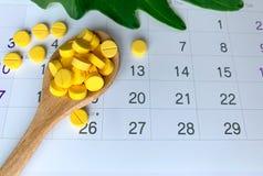Des comprimés foliques sur une cuillère en bois sont placés sur le calendrier image libre de droits