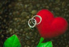 Des couples argentés d'anneau de fond sont placés sur les coeurs et le café rouges bruit de fond et brouillé Image stock