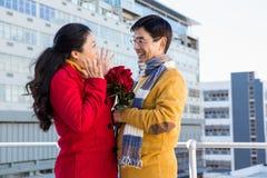 Des couples asiatiques plus anciens sur le balcon avec des roses Photographie stock