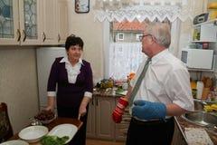 Des couples plus anciens faisant cuire dans la cuisine Image stock