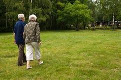 Des couples plus anciens marchant par un stationnement Photo stock