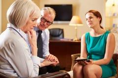 Des couples plus anciens parlant au conseiller à l'aide de la Tablette de Digital Photographie stock libre de droits
