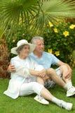 Des couples plus anciens se reposant près des fleurs Photos libres de droits