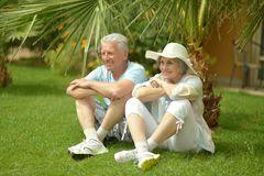 Des couples plus anciens se reposant près des fleurs Images stock