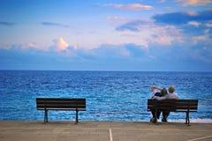 Des couples plus anciens sur des sentiments d'un banc de l'amour Photos stock