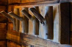Des crochets en bois sont fixés à un mur de bois Image libre de droits