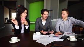 Des directeurs sérieux, deux hommes et les femmes sont chargés du travail, technologie d'utilisation et se reposent au bureau ave
