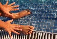 Des doigts et les tep évasés sont frappés légèrement dans l'eau Photographie stock libre de droits