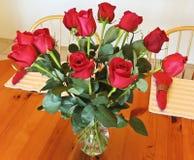 Des douzaine roses rouges dans un vase en cristal Photo stock