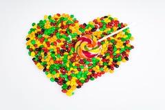 Des dragées à la gelée de sucre colorées sont dispersées sous forme de coeur et lucette sous forme de flèche sur un fond blanc Photo libre de droits