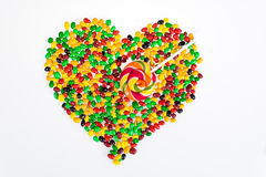 Des dragées à la gelée de sucre colorées sont dispersées sous forme de coeur et lucette sous forme de flèche sur un fond blanc Images libres de droits
