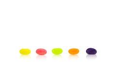Des dragées à la gelée de sucre de couleur sont alignées dans les rangées sur le fond blanc image libre de droits