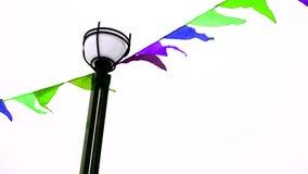 Des drapeaux triangulaires colorés flottant dans le vent sont attachés à une décoration de lampadaire pour des vacances, extérieu banque de vidéos