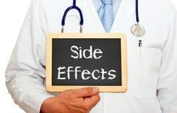 Des effets secondaires - soignez tenir le tableau avec le texte images stock