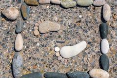 Des empreintes de pas en pierre sont jointes dans un cadre Photos libres de droits