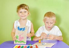 Des enfants sont moulés de l'argile coloré Image stock