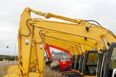 Des excavatrices jaunes sont situées dans une rangée images stock