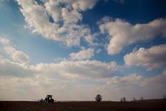 Des Feldtraktors des blauen Himmels oben genannter gepflogener einzelner Baum auf Skylinen Lizenzfreies Stockfoto