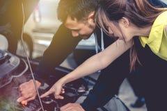 Des femmes asiatiques qui sont les voitures endommagées sont aidées par un homme qui image stock