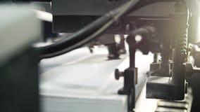 Des feuilles de papier imprimées sont servies dans la presse typographique Compensation, CMYK, fin  photographie stock libre de droits
