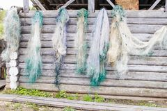 Des filets de pêche sont séchés sur un mur de rondin photographie stock