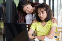 Des filles asiatiques sont soumises à une contrainte avec les travaux pour lesquels ne comprenez pas et ayez les amis à encourage Images libres de droits